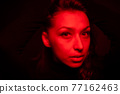 Young pretty woman looks at camera in contrast red light, sensual fashion beauty 77162463