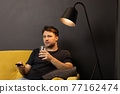 Young unshaven guy watching movie on TV on sofa with drink and remote control 77162474
