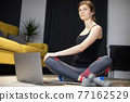 Concentrated young woman practicing yoga on mat with knees bent turning head 77162529