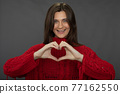 Happy smiling woman showes heart with hands joyfully looks at camera, copy space 77162550
