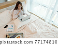 Woman working on laptop in bed 77174810