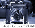 3D printer printing a model in the form of black vase close-up. 77174960