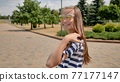 A young teenager girl poses in a summer day in a striped dress. 77177147