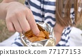 The girl eats chips in the city park in the summer. The girl eats chips in the city park in the summer. Package with chips close-up. 77177153