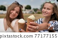 Two girls are presenting ice cream to the viewer. 77177155