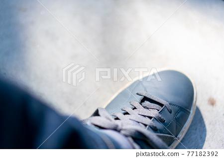 Men's feet in sneakers 77182392
