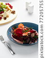 Beet summer salad with arugula, radicchio, soft cheese and walnuts on plate dressing and spices on blue plate, copy space, top view 77205755