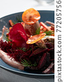 Beet summer salad with arugula, radicchio, soft cheese and walnuts on plate dressing and spices on blue plate, copy space, top view 77205756