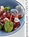 Beet summer salad with arugula, radicchio, soft cheese and walnuts on plate dressing and spices on blue plate, copy space, top view 77205757