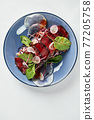 Beet summer salad with arugula, radicchio, soft cheese and walnuts on plate dressing and spices on blue plate, copy space, top view 77205758