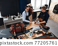 leather craftsmen working making measupenets in patterns at table in workshop studio 77205761