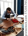 leather craftsmen working making measupenets in patterns at table in workshop studio 77205765