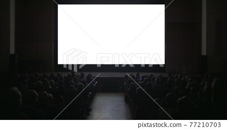 Viewers in dark cinema hall with blank screen 77210703