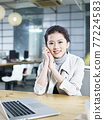 young asian businesswoman sitting at desk in office looking at camera smiling 77224583
