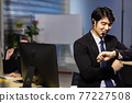 Businessman looking at the time on his wrist watch in call center office. 77227508
