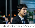 Businessman working overtime late at night in call center office with colleague team. 77227512