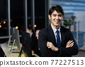 Businessman working overtime late at night in call center office with colleague team. 77227513