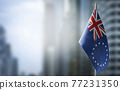 A small flag of Cook Islands on the background of a blurred background 77231350