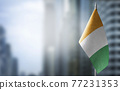 A small flag of Cote dIvoire on the background of a blurred background 77231353