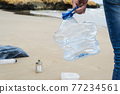 collecting a used plastic bottle on the beach 77234561