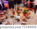 Flower and candle decoration for a wedding against the background of dancing guests 77240445