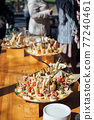 Sandwiches, canapes and cakes on the festive table. A wide variety of snacks 77240461