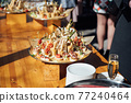 Sandwiches, canapes and cakes on the festive table. A wide variety of snacks 77240464