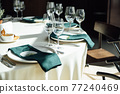 Luxurious restaurant. Luxurious interior, white tables, serving dishes and glasses for guests 77240469