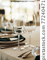 Luxurious restaurant. Luxurious interior, white tables, serving dishes and glasses for guests 77240471