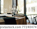 Luxurious restaurant. Luxurious interior, white tables, serving dishes and glasses for guests 77240474