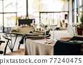 Luxurious restaurant. Luxurious interior, white tables, serving dishes and glasses for guests 77240475
