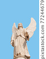 Cover page with statue of winged angel at Evangelical church Saint Nikolai with copy space for text and blue sky as solid background, Potsdam, Germany. Concept of religious and historical heritage. 77244679