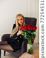 Attractive blonde model in black touching red 77254531