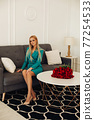 Posh blonde on sofa in living room with bouquet. 77254533