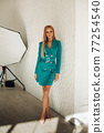 Attractive blonde in green formal dress with belt. 77254540