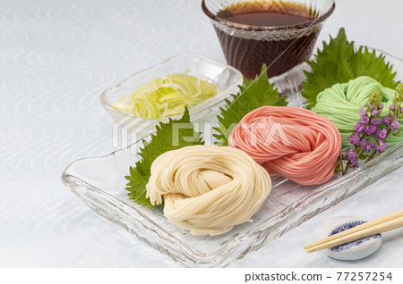 Colored somen served on a glass plate 77257254