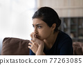 Close up unhappy Indian woman lost in thoughts, sitting alone 77263085