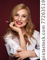 Portrait of a beautiful elderly woman in a white shirt with classic makeup and blond hair. 77263519