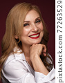 Portrait of a beautiful elderly woman in a white shirt with classic makeup and blond hair. 77263529