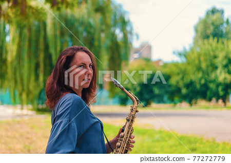 cute young redhead woman posing with saxophone in city park 77272779