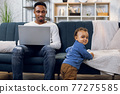 Afro american man working on laptop and taking care of son 77275585