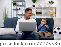 Afro father sitting with son on couch and working on laptop 77275586