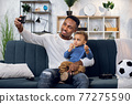 Happy father and son taking selfie on smartphone at home 77275590
