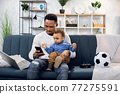 Father and son using smartphone while sitting on couch 77275591