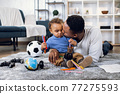 Young father and son playing with toys on carpet 77275593