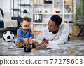 Afro american father and son drawing with pencils on floor 77275603