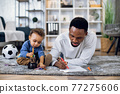 Afro american father and son drawing with pencils on floor 77275606
