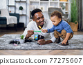 Young father and son drawing with pencils at home 77275607