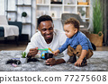 Young father and son drawing with pencils at home 77275608
