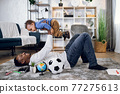 Cheerful man lying on carpet and playing with baby boy 77275613